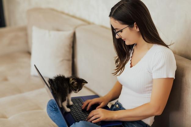 Mulher jovem feliz de óculos está trabalhando em um laptop enquanto está sentada em um sofá confortável em casa com um gatinho engraçado
