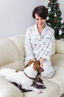 Mulher jovem feliz de pijama com cachorro adorável na sala com árvore de natal. feriados