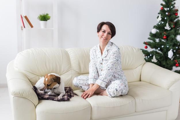Mulher jovem feliz de pijama com cachorro adorável na sala de estar com árvore de natal