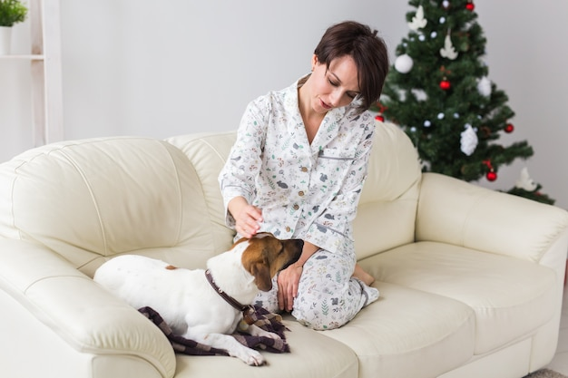 Mulher jovem feliz de pijama na sala de estar com árvore de natal. conceito de férias.