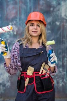 Mulher jovem feliz de uniforme segurando um rolo de pintura perto da parede colorida