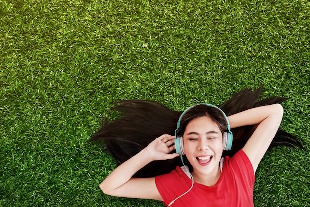 Mulher jovem feliz deitado na grama verde para ouvir música via fone de ouvido no parque
