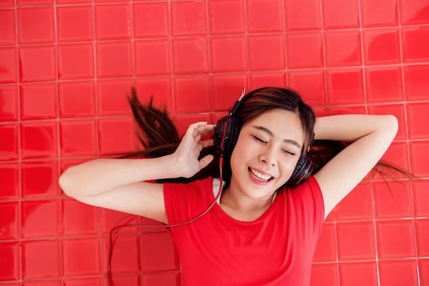 Mulher jovem feliz deitado no chão vermelho para ouvir música via fone de ouvido na sala