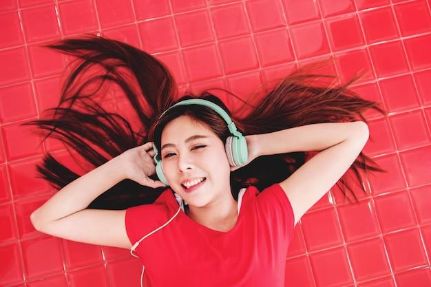 Mulher jovem feliz deitado no chão vermelho para ouvir música via fone de ouvido.