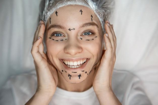 Mulher jovem feliz, deitado no sofá na tampa. ela toca seu rosto, sorri e olha. modelo tem marcas na pele.