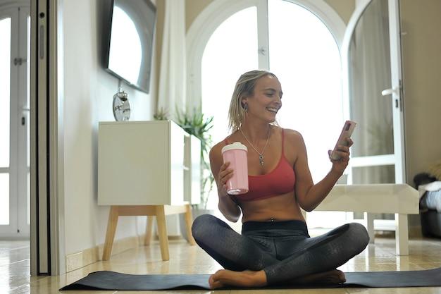 Mulher jovem feliz descansando na esteira de ioga bebendo água e verificando o telefone