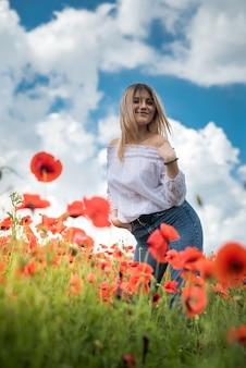 Mulher jovem feliz desfrutando de liberdade na natureza, campo de papoulas. horário de verão