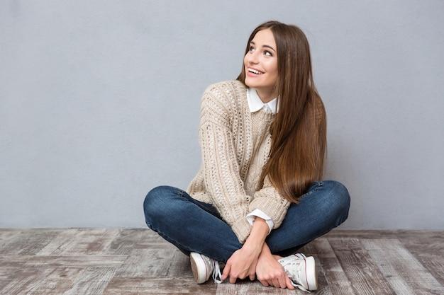 Mulher jovem feliz e animada com cabelo comprido, vestindo uma blusa bege e jeans, sentada no chão de madeira com as pernas cruzadas e olhando para longe