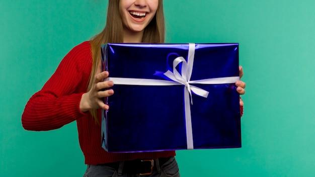 Mulher jovem feliz e animada com chapéu de papai noel com caixa de presente sobre fundo azul - imagem