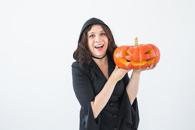Mulher jovem feliz e animada com fantasia de halloween posando com abóbora esculpida no lightroom