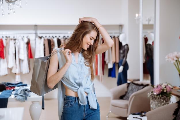 Mulher jovem feliz e animada com sacolas de compras em loja de roupas