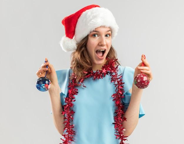 Mulher jovem feliz e animada com uma blusa azul e um chapéu de papai noel com enfeites em volta do pescoço segurando bolas de natal e sorrindo alegremente