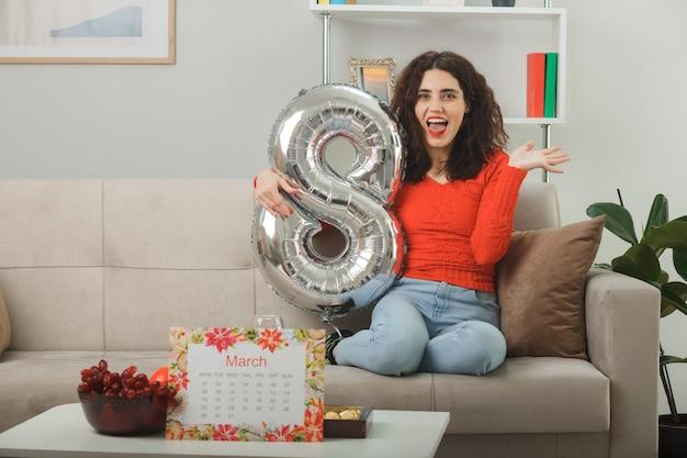 Mulher jovem feliz e animada em roupas casuais, sorrindo alegremente sentada em um sofá com um balão em forma de número oito na sala de estar iluminada, celebrando o dia internacional da mulher, 8 de março
