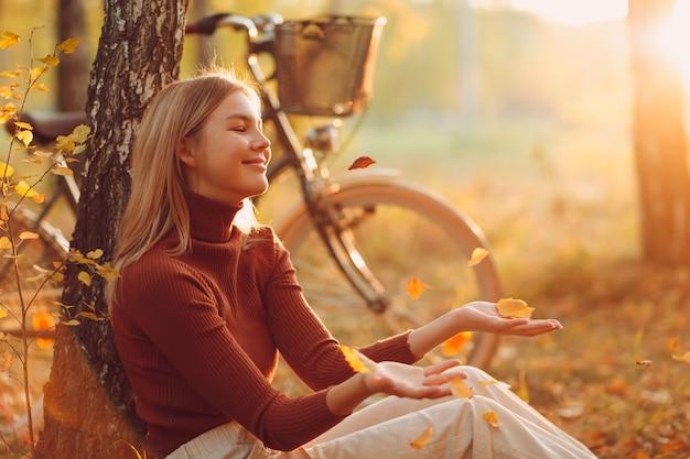 Mulher jovem feliz e ativa sentada com uma bicicleta vintage no parque de outono ao pôr do sol