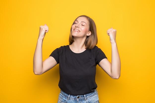 Mulher jovem feliz e bem-sucedida com as mãos levantadas, gritando e comemorando o sucesso na parede amarela