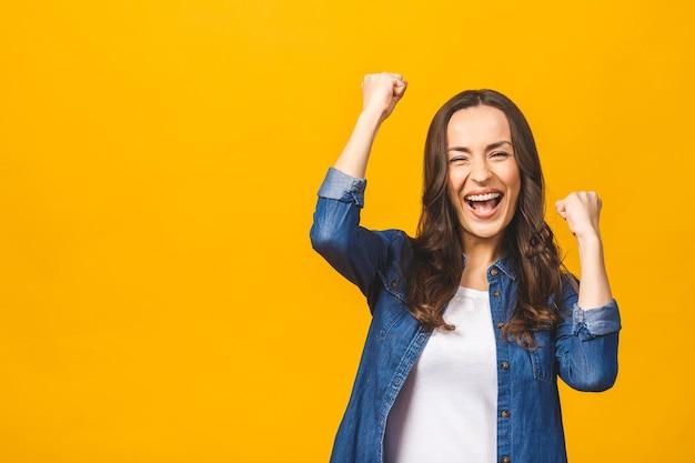 Mulher jovem feliz e bem sucedida com as mãos levantadas, gritando e comemorando o sucesso