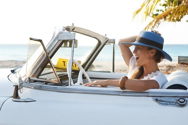 Mulher jovem feliz e carro conversível retrô ao lado da praia na cidade de varadero