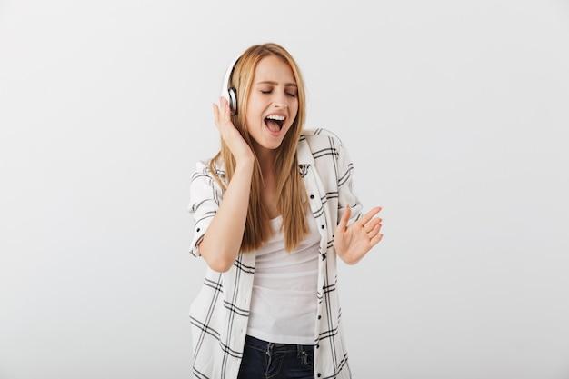 Mulher jovem feliz e casual ouvindo música com fones de ouvido