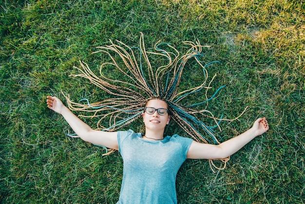 Mulher jovem feliz é deitado na grama com tranças de caixa dispostas como sol, aproveitando os dias de verão