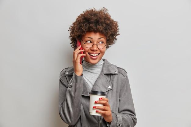 Mulher jovem feliz e despreocupada com cabelo afro, conversa animada ao telefone, desvia o olhar, segura uma xícara descartável de café, usa óculos redondos e jaqueta cinza