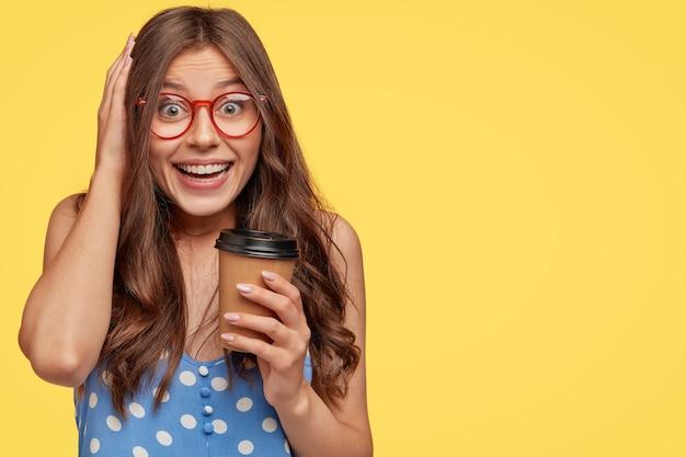 Mulher jovem feliz e encantada ri positivamente, usa óculos redondos