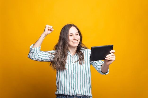 Mulher jovem feliz e espantada em casual comemorando a vitória e segurando o tablet.