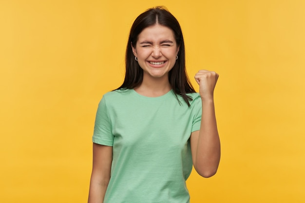 Mulher jovem feliz e inspirada com cabelo escuro e mão levantada em camiseta menta se sentindo animada e comemorando a vitória isolada sobre a parede amarela