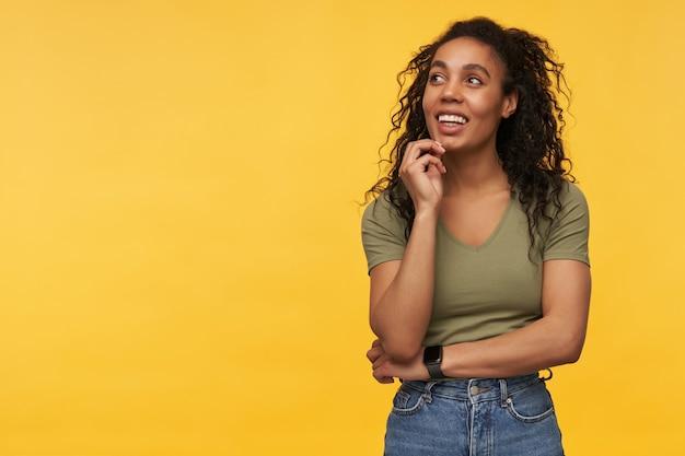 Mulher jovem feliz e pensativa em roupas casuais, olhando para o lado no espaço vazio e pensando isolada sobre a parede amarela