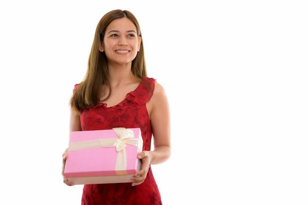 Mulher jovem feliz e pensativa sorrindo e segurando uma caixa de presente