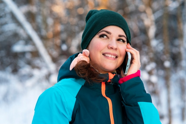 Mulher jovem feliz e positiva caminhando no parque em um dia frio e ensolarado de inverno e falando no celular dela