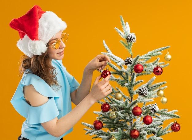 Mulher jovem feliz e positiva com top azul e chapéu de papai noel usando óculos amarelos, decorando a árvore de natal em pé sobre a parede laranja