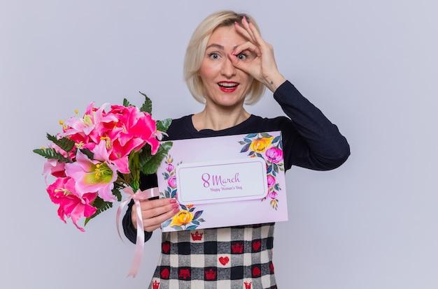 Mulher jovem feliz e positiva segurando um cartão e um buquê de flores olhando por entre os dedos fazendo sinal de ok sorrindo celebrando a marcha do dia internacional da mulher