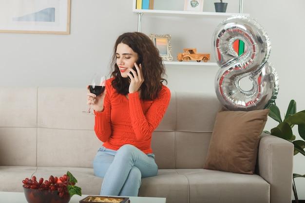 Mulher jovem feliz e satisfeita com roupas casuais, sorrindo alegremente sentada em um sofá com uma taça de vinho, falando no celular na sala de estar iluminada, celebrando o dia internacional da mulher, 8 de março