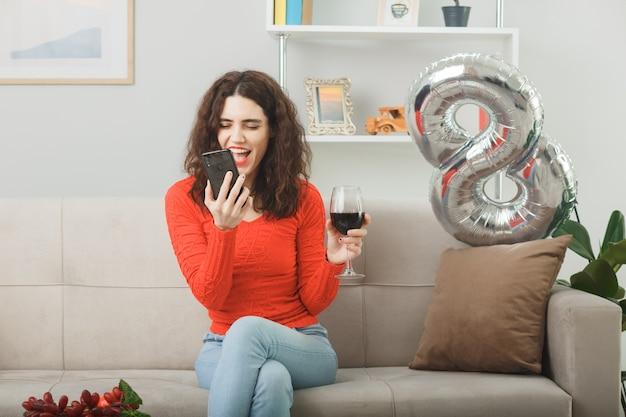 Mulher jovem feliz e satisfeita em roupas casuais, sorrindo alegremente sentada em um sofá com uma taça de vinho falando no celular na sala de estar iluminada, celebrando o dia internacional da mulher, 8 de março