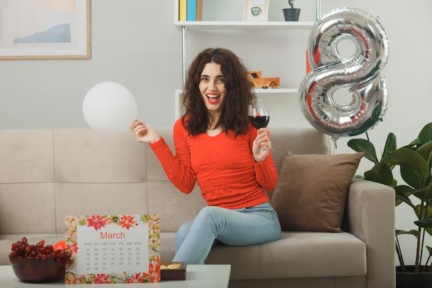 Mulher jovem feliz e satisfeita em roupas casuais, sorrindo alegremente sentada em um sofá com uma taça de vinho segurando um balão na sala de estar iluminada, celebrando o dia internacional da mulher, 8 de março