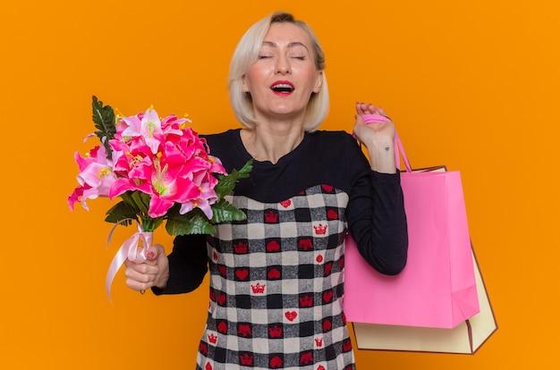 Mulher jovem feliz e satisfeita em um lindo vestido segurando um buquê de flores e sacos de papel com presentes comemorando o dia internacional da mulher em pé sobre a parede laranja
