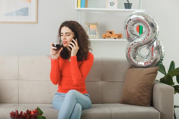 Mulher jovem feliz e satisfeita, sorrindo alegremente, sentada em um sofá com uma taça de vinho, falando no celular em uma sala iluminada, celebrando o dia internacional da mulher, 8 de março.