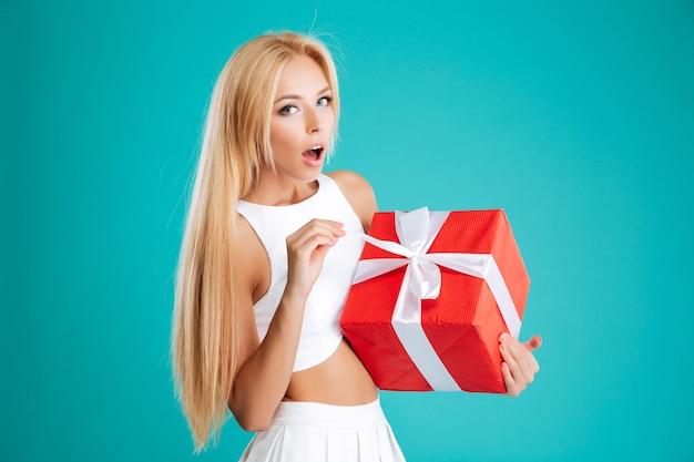 Mulher jovem feliz e surpresa abrindo uma caixa de presente vermelha sobre fundo azul
