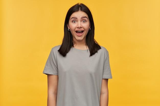 Mulher jovem feliz e surpresa com cabelo escuro e boca aberta em uma camiseta cinza parece animada com a parede amarela