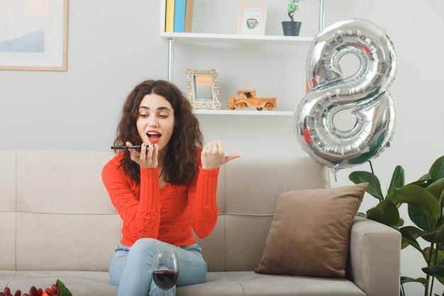 Mulher jovem feliz e surpresa em roupas casuais, sorrindo alegremente sentada em um sofá com uma taça de vinho, falando no celular na sala de estar iluminada, celebrando o dia internacional da mulher, 8 de março