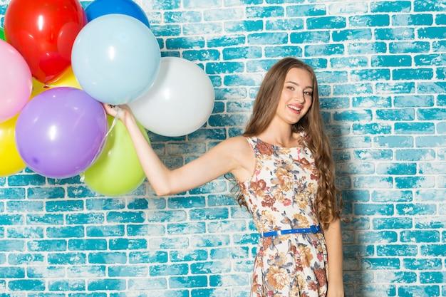 Mulher jovem feliz, em cima de parede azul e segurando balões