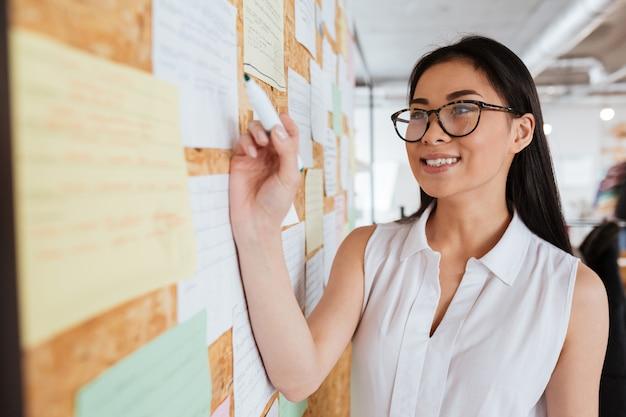 Mulher jovem feliz em copos, escrevendo o anúncio no quadro de avisos