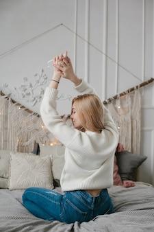 Mulher jovem feliz em fones de ouvido, ouvindo música do smartphone e dançando na cama em casa