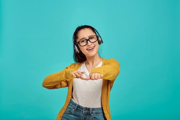 Mulher jovem feliz em fones de ouvido, parede azul, emoção. expressão facial, pessoa do sexo feminino olhando para a câmera no estúdio, conceito emocional, sentimentos positivos