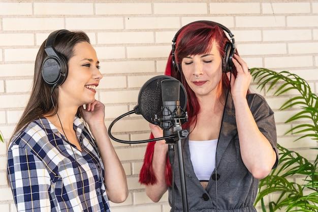 Mulher jovem feliz em fones de ouvido, sorrindo e ouvindo a namorada cantando com os olhos fechados enquanto grava música contra uma parede de tijolos no estúdio