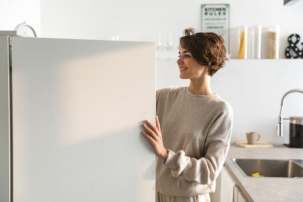 Mulher jovem feliz em frente à geladeira aberta