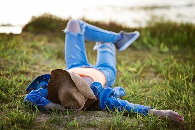 Mulher jovem feliz em jeans e chapéu de cowboy ao pôr do sol encontra-se na costa da baía