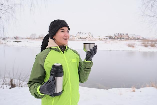 Mulher jovem feliz em luvas quentes de pé na margem do rio e bebendo chá quente durante uma caminhada