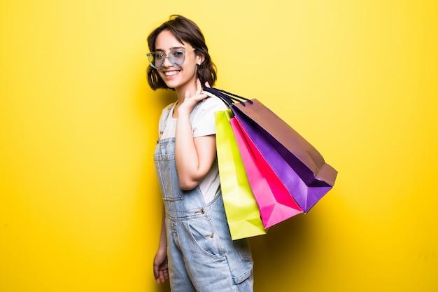 Mulher jovem feliz em óculos de sol segurando sacolas de compras.