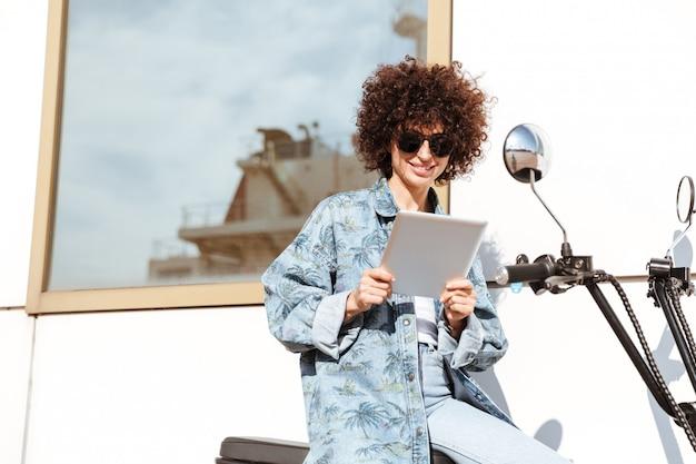 Mulher jovem feliz em óculos de sol usando computador tablet